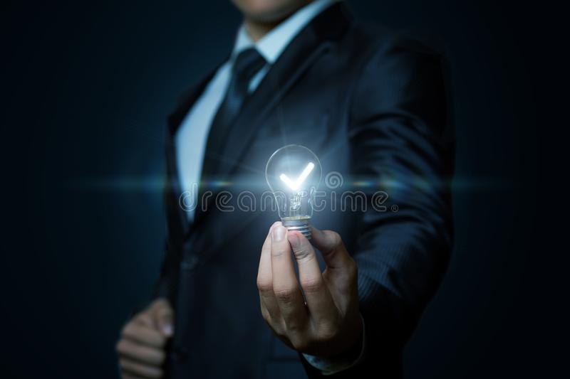 The concept is the creative idea. A businessman is showing a glowing lightbulb in his hand at the dark background. The concept is the creative idea stock image