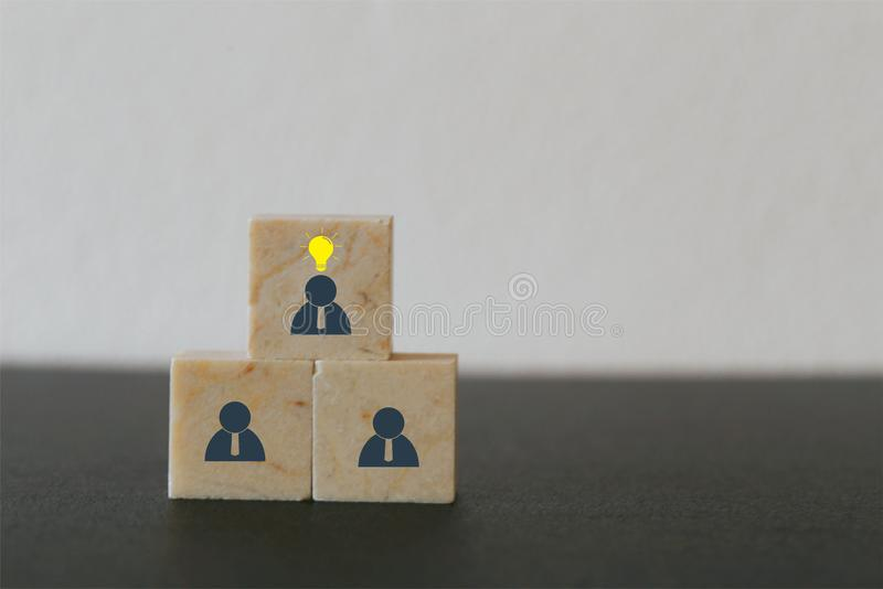 Concept creative idea, leader with idea and innovation. Marble block stacking with human symbol and light bulb icon.  stock photography