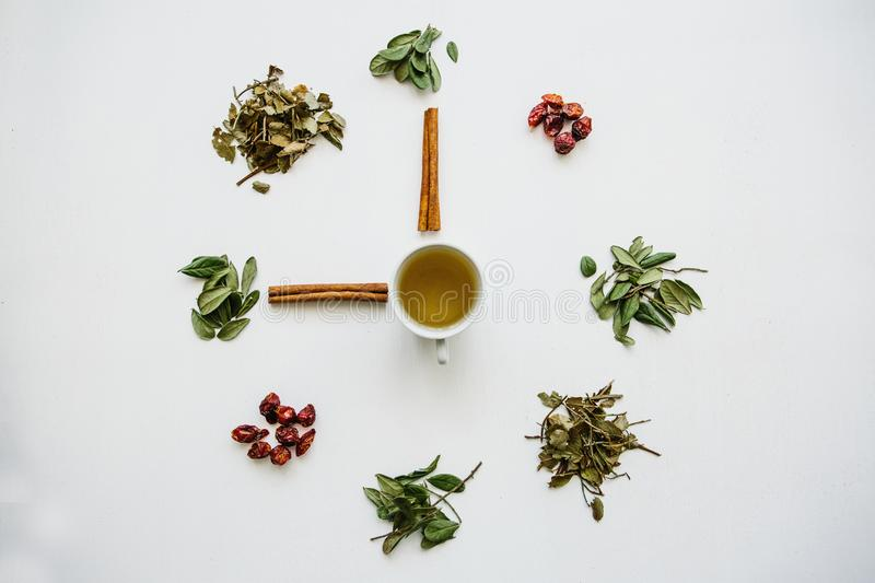 A concept or creative idea that means tea time. Useful herbal or green tea in the center and around the various dried royalty free stock photography