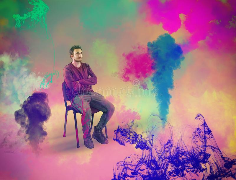 The concept of creativity and visualization. Young man sitting on chair while he visualize colorful ink and steam. The concept of creativity and visualization stock photos