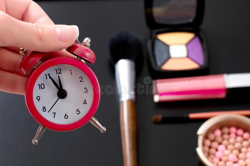 Concept cropped image with cosmetic and make up products. Quick make-up. Red retro clock. Selective focus.  royalty free stock photography