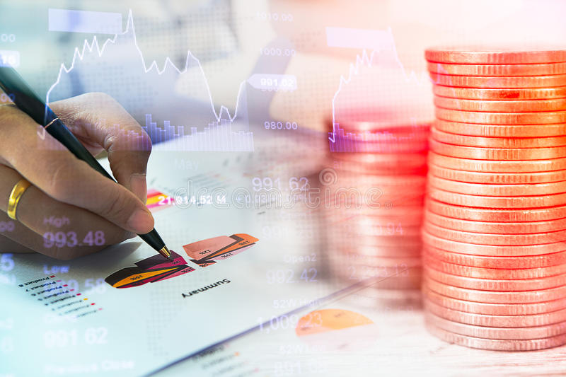 Concept of currency trading. Stack of coins and a hand holding is examining a technical chart of financial instrument stock image