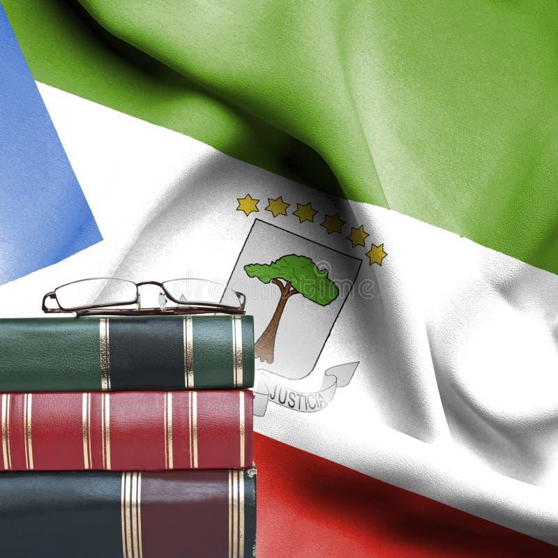 Concept d'éducation - pile de livres et de verres de lecture contre le drapeau national de l'Érythrée Guinée photo stock