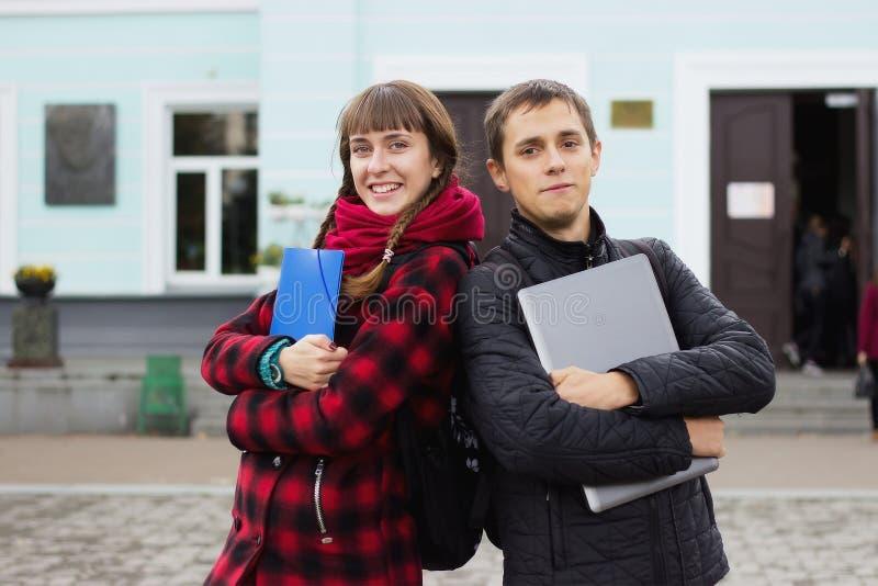 Concept d'étudiants - le garçon et la fille vous invitent à étudier image libre de droits