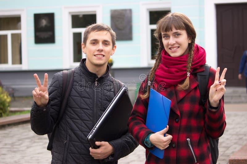 Concept d'étudiants - le garçon et la fille vous invitent à étudier photographie stock
