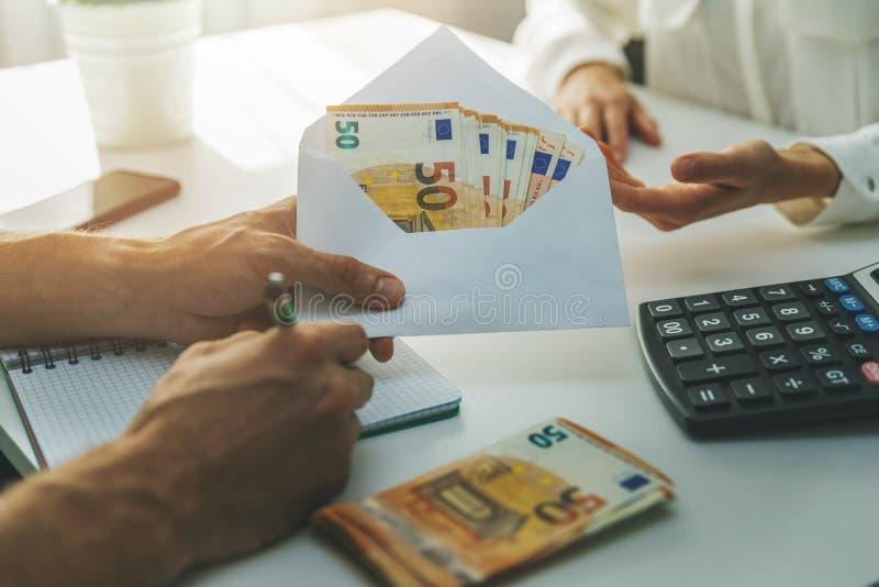 Concept d'évasion fiscale pour l'emploi illégal - enveloppe de don de main-d'oeuvre avec de l'argent comptant image libre de droits