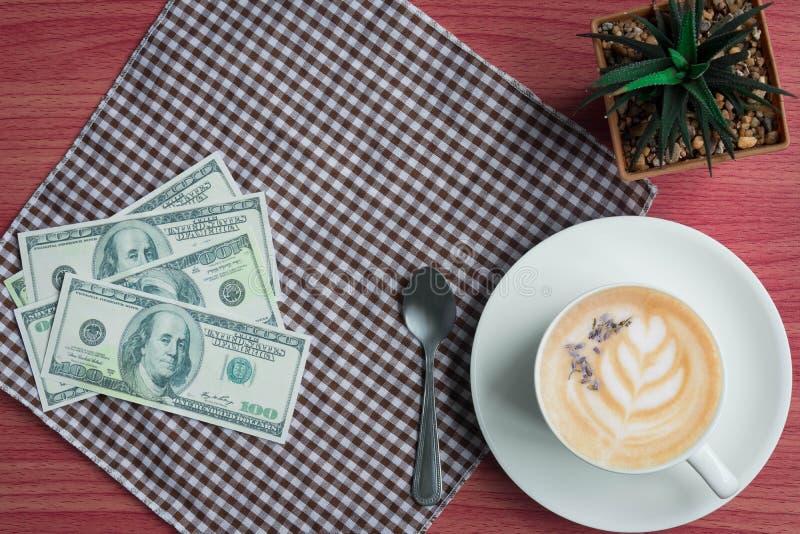Concept d'affaires avec du café, l'argent, le cactus et le tissu sur la table en bois rose photographie stock