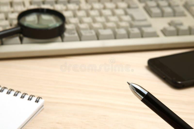 Concept d'affaires Bloc-notes, téléphone intelligent, et loupe avec le clavier d'ordinateur photographie stock