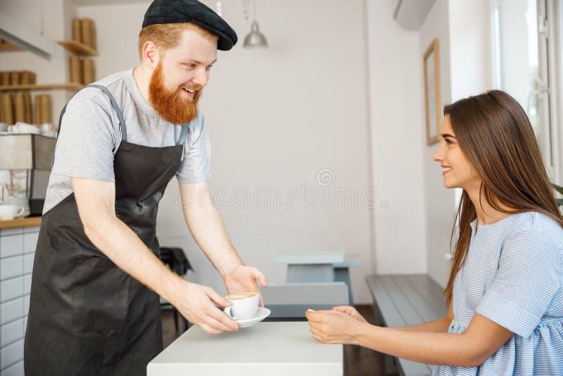 Concept d'affaires de café - serveur ou barman servant le café chaud et parlant avec la belle dame caucasienne dans la robe bleue images stock
