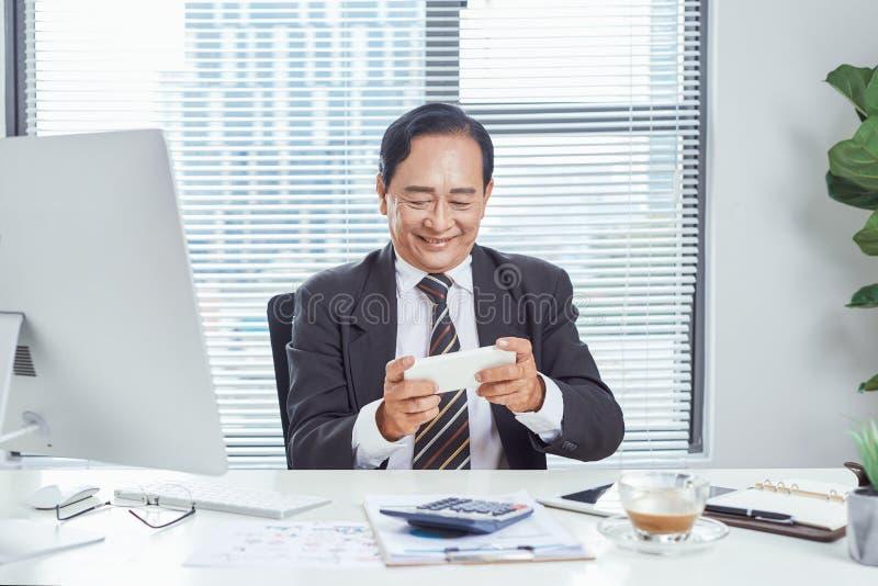 Concept d'affaires, de communication et de technologie - homme d'affaires ? l'aide du smartphone au bureau photos stock