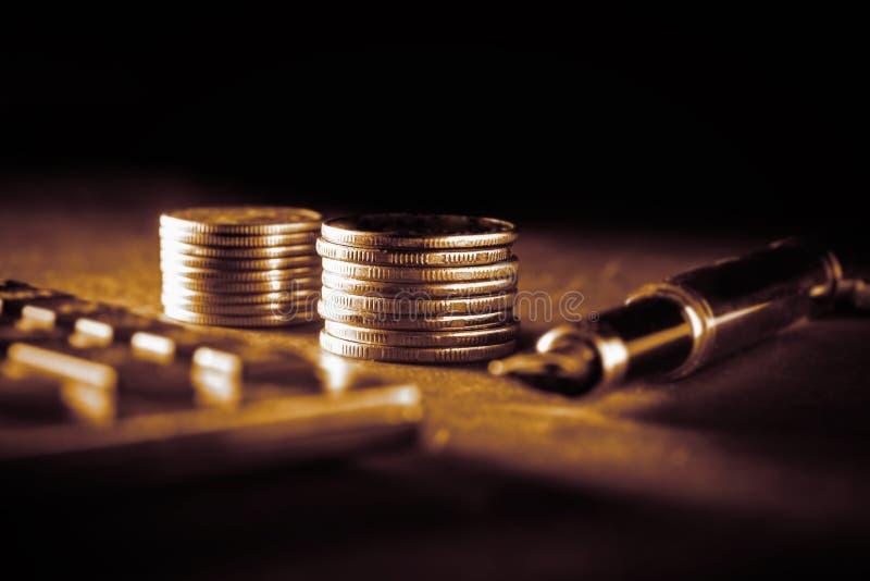 Concept d'affaires, de finances ou d'investissement Groupes de pièces de monnaie à côté de stylo-plume et de calculatrice Fond mo photo libre de droits