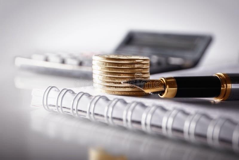 Concept d'affaires, de finances ou d'investissement Pièces de monnaie, carnet de livre de chèque ou et stylo-plume, calculatrice  photo libre de droits