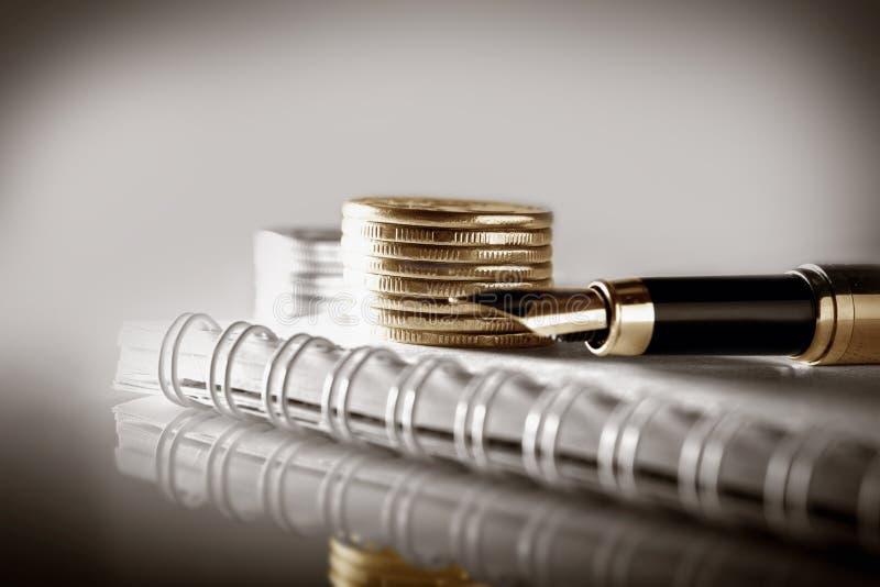 Concept d'affaires, de finances ou d'investissement Pièces de monnaie, carnet de livre de chèque ou et stylo-plume La lumière a m image stock