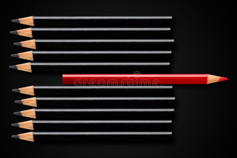 Concept d'affaires de rupture, direction ou penser différent ; crayon rouge dans la rangée des crayons noirs se dirigeant dans la images stock