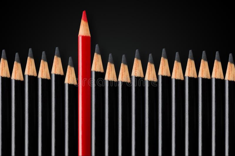Concept d'affaires de rupture, direction ou penser différent ; crayon rouge devant la rangée des crayons noirs se tenant  photo stock