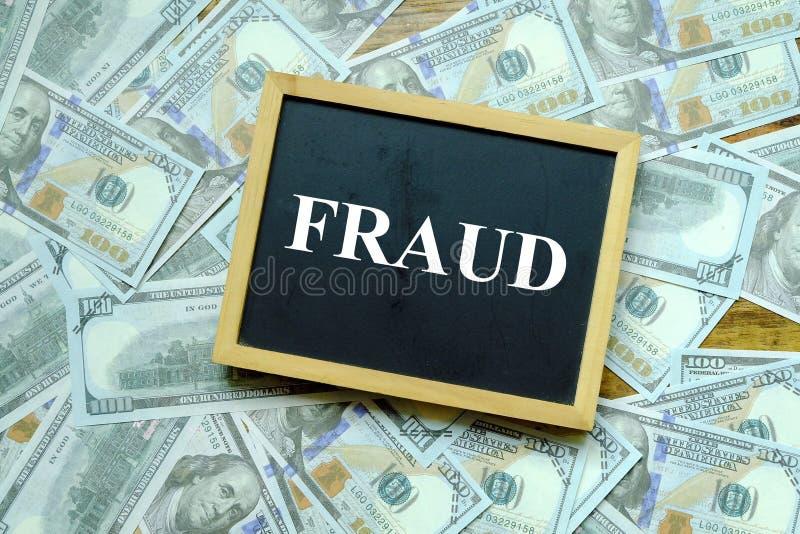 Concept d'affaires et de finances Vue supérieure de tableau noir écrite avec la FRAUDE avec cent billets de banque du dollar au f photo libre de droits