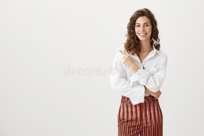 Concept d'affaires et de succès Portrait de la fille influente attirante souriant largement tout en indiquant à gauche avec photographie stock