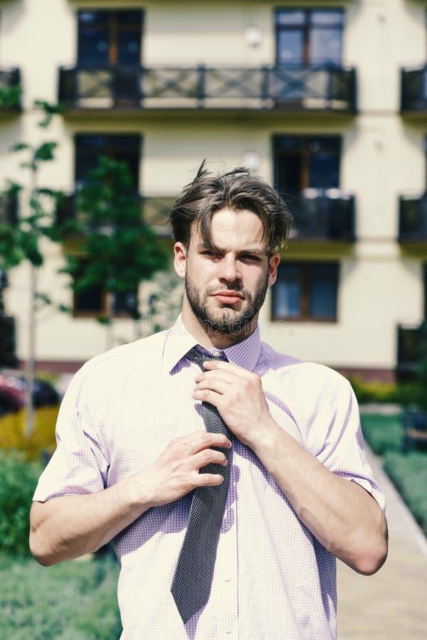 Concept d'affaires et d'immobiliers Jeune homme ou agent immobilier dans la cour de la maison de rapport le jour ensoleillé Homme photographie stock libre de droits