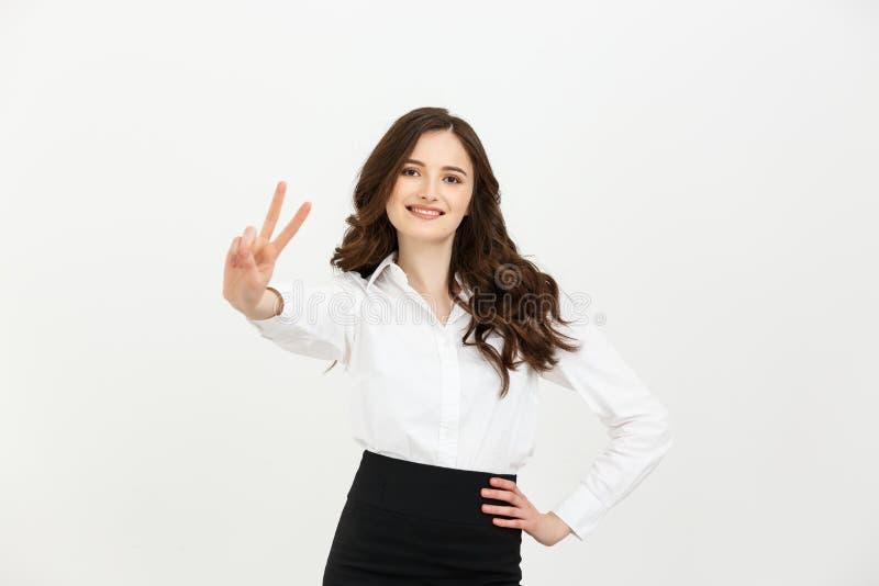 Concept d'affaires : Femme d'affaires montrant le signe de victoire et souriant au-dessus du fond blanc photographie stock libre de droits