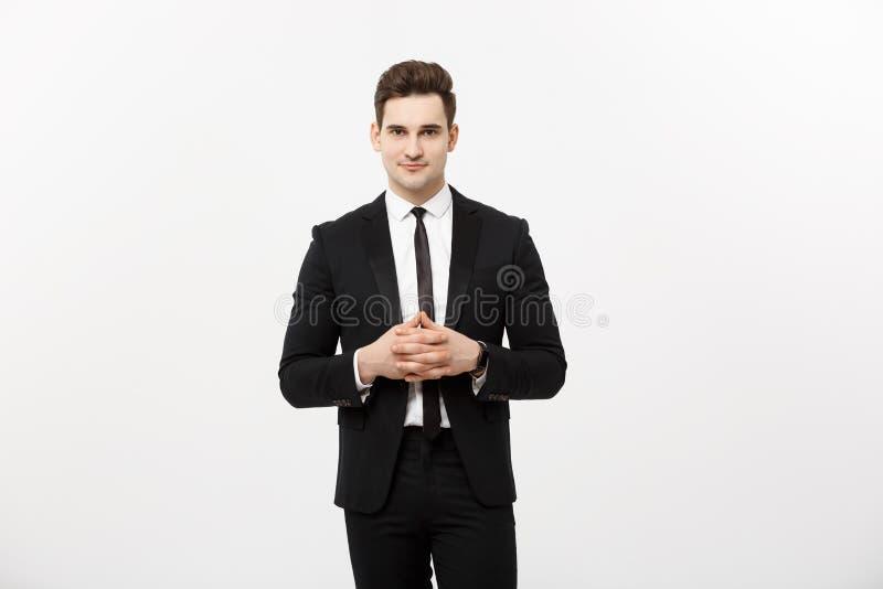 Concept d'affaires - homme bel d'affaires de portrait dans le costume tenant des mains avec le visage sûr Fond blanc photos stock