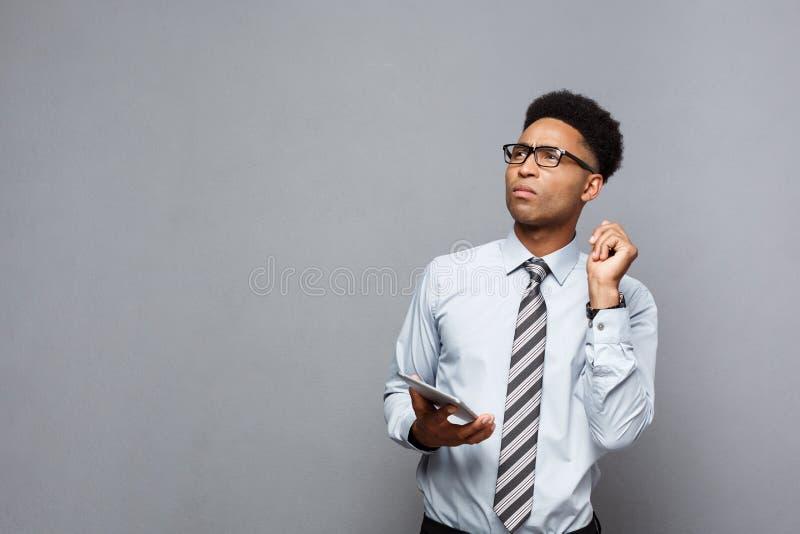 Concept d'affaires - homme d'affaires professionnel bel heureux d'afro-américain choquant et pensant avec le comprimé numérique d photos libres de droits