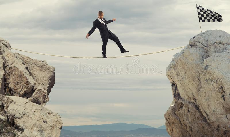 Concept d'affaires d'homme d'affaires qui surmontent les problèmes atteignant le drapeau sur une corde photos stock