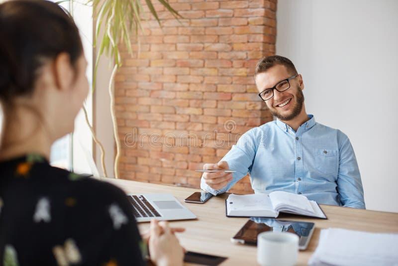 Concept d'affaires Jeune brune s'asseyant devant le directeur de bureau gai mûr sur l'entrevue d'emploi, ayant photographie stock libre de droits
