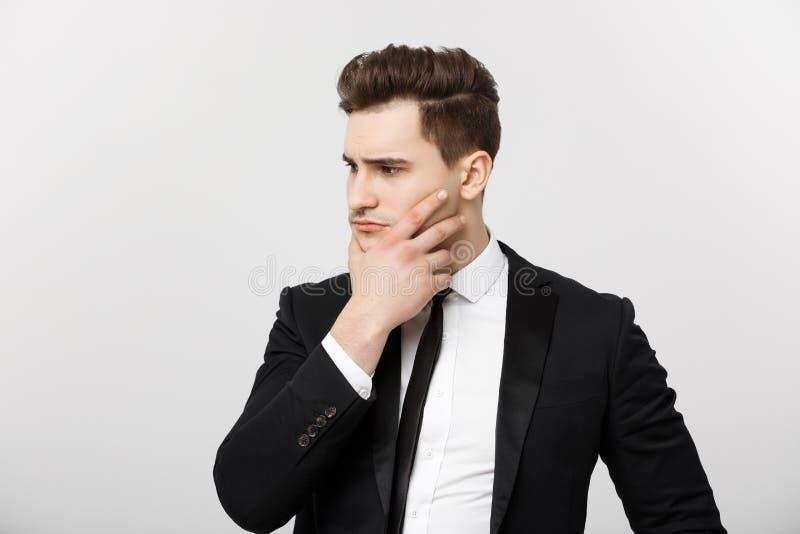 Concept d'affaires : Jeune homme d'affaires bel dans le costume pensant avec la main sur le menton, concept de stratégies commerc image libre de droits