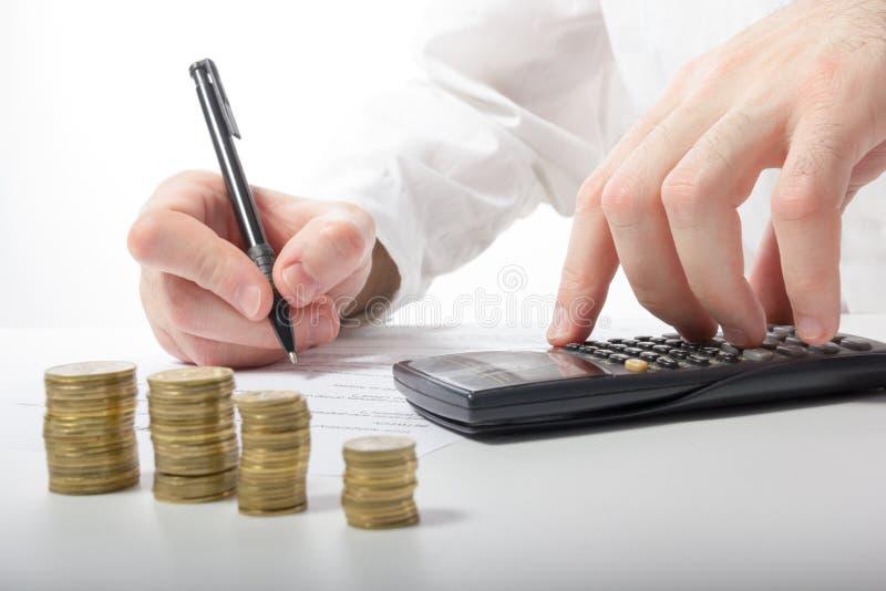Concept d'affaires La main de l'homme d'affaires comptant l'argent sur le calculato photos libres de droits