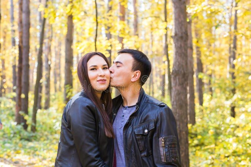 Concept d'amour, de relations, de famille et de personnes - équipez embrasser son épouse en parc d'automne photographie stock libre de droits