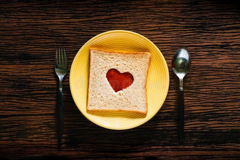 Concept d'amour et de romance Pain de plat avec la cuillère et fourchette dans le temps de petit déjeuner Forme de coeur avec la  photo stock