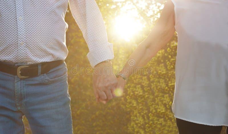 Concept d'amour LES PERSONNES ÂGÉES COUPLENT TENIR DES MAINS SUR LE COUCHER DU SOLEIL Plan rapproché photo stock