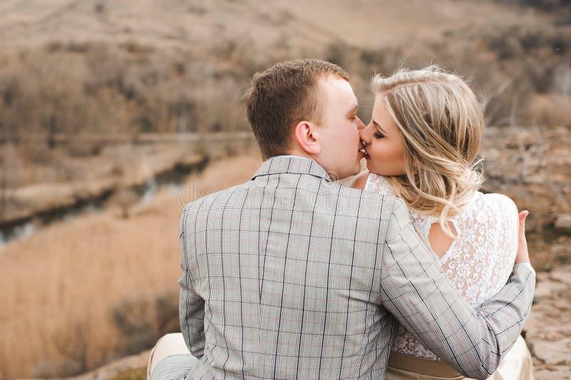 Concept d'amour, roman et de personnes - jeune couple heureux étreignant la séance au bord d'une falaise dehors photo stock
