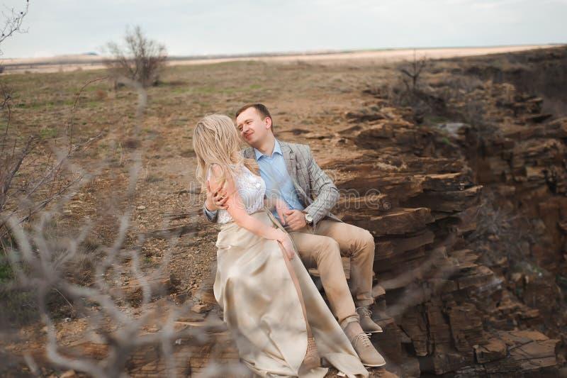 Concept d'amour, roman et de personnes - jeune couple heureux étreignant la séance au bord d'une falaise dehors image stock