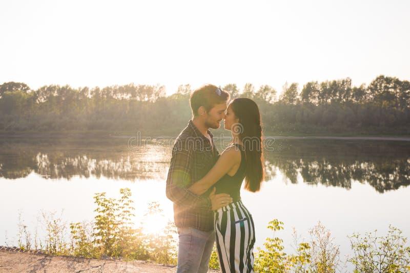 Concept d'amour, romantique et de nature - jeune couple étreignant près du lac photographie stock libre de droits