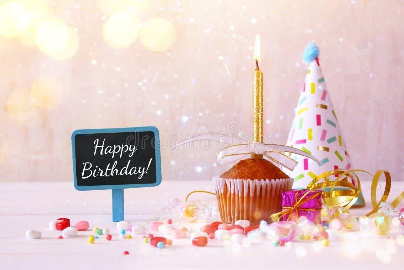 Concept d'anniversaire avec le petit gâteau et la bougie à côté de peu de chalkboa images stock