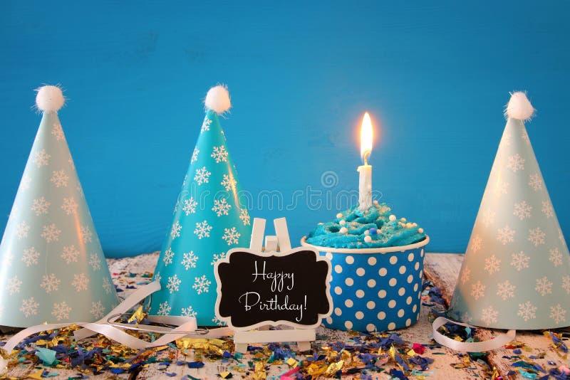 Concept d'anniversaire avec le petit gâteau et la bougie sur la table en bois photos stock