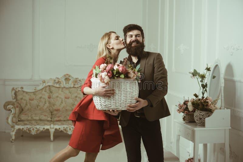 Concept d'anniversaire L'homme barbu de baiser sensuel de femme avec l'anniversaire fleurit L'homme barbu donnent le panier avec  images libres de droits