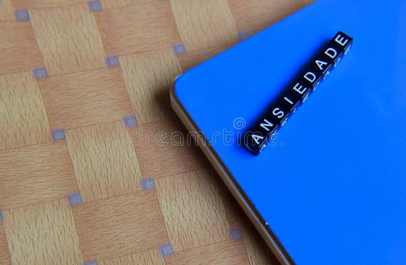 Concept d'Ansiedade dans le Portugais sur les cubes en bois avec des livres à l'arrière-plan photos stock