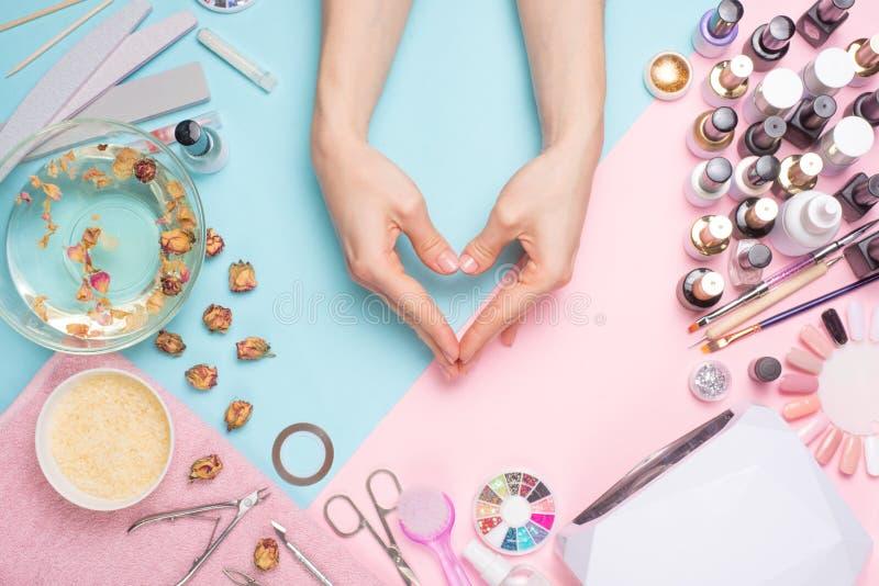 Concept d'art de clou Une femme se donne une manucure sur la table Mains en forme de coeur image libre de droits