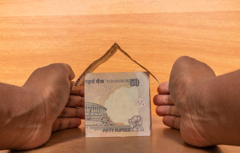 Concept d'assurance des biens, mains protégeant la maison faite avec la devise de papier indienne photo stock