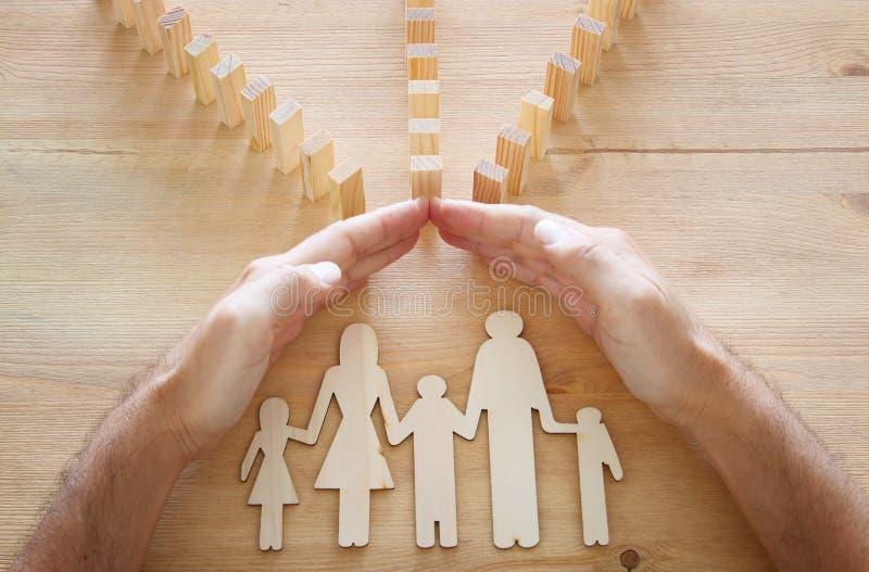 Concept d'assurance Homme d'affaires protégeant une famille contre l'effet de domino la vie, financier et problèmes de santé photographie stock libre de droits