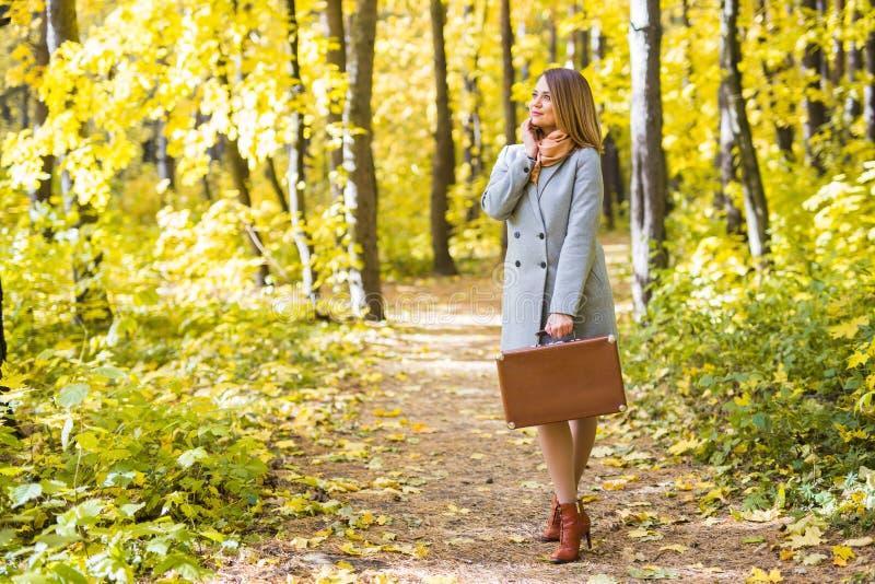 Concept d'automne, de nature et de personnes - jeune belle femme dans le manteau gris en nature de chute photos stock
