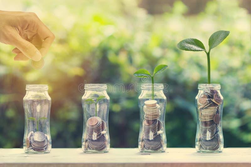 Concept d'?conomie et d'investissement Pièce de monnaie de participation de main au-dessus de la pile de pièces de monnaie dans l images stock