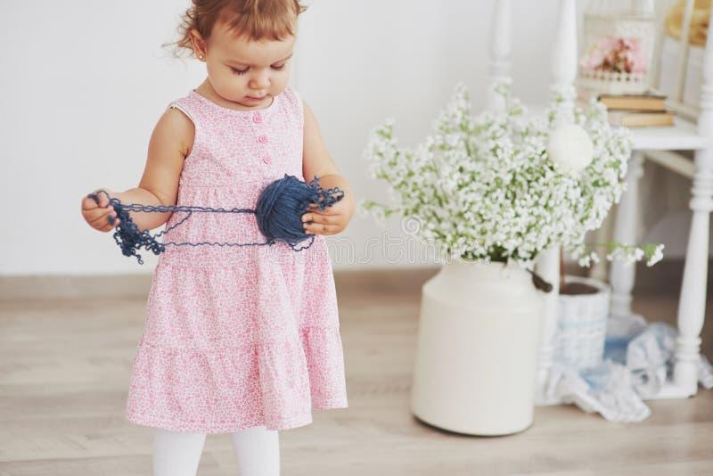 Concept d'enfance Bébé dans le jeu mignon de robe avec le fil coloré Childroom blanc de vintage images stock