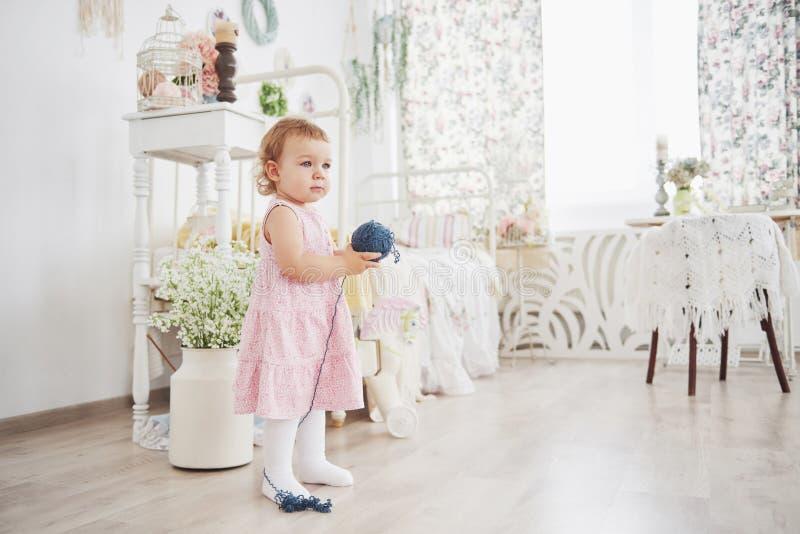 Concept d'enfance Bébé dans le jeu mignon de robe avec le fil coloré Childroom blanc de vintage photos stock