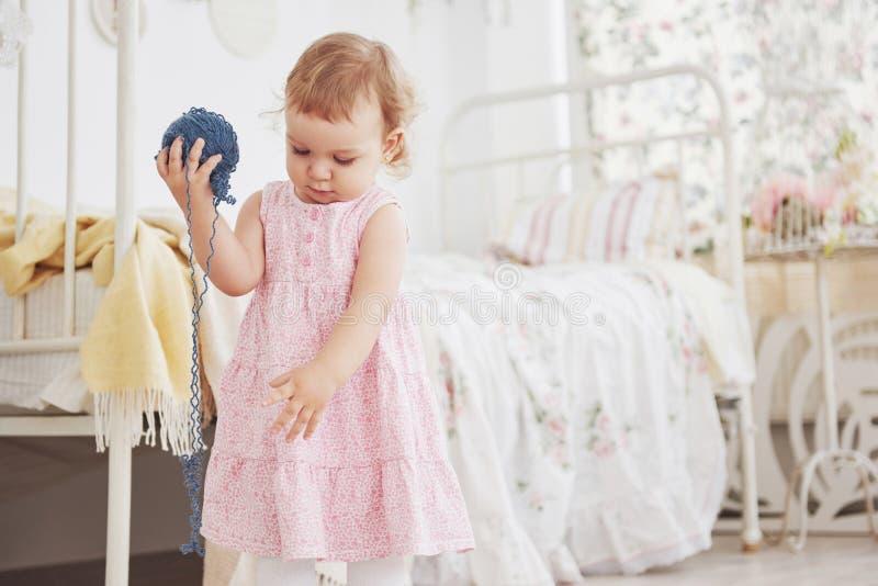 Concept d'enfance Bébé dans le jeu mignon de robe avec le fil coloré Childroom blanc de vintage images libres de droits