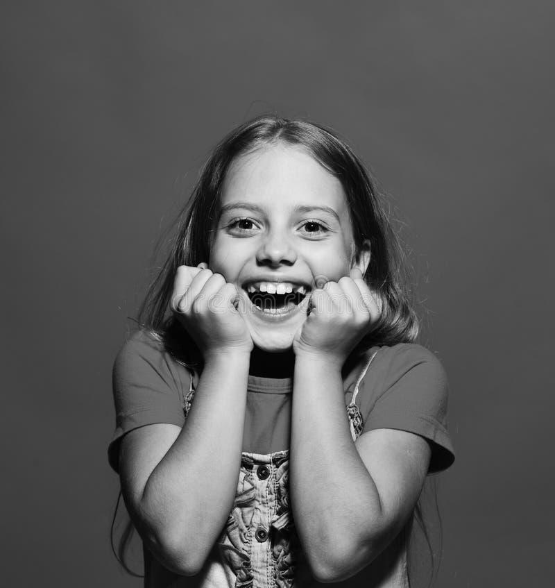 Concept d'enfance et de bonheur Enfant avec le visage gai et les cheveux justes L'enfant tire ses joues dans l'excitation Fille photographie stock libre de droits