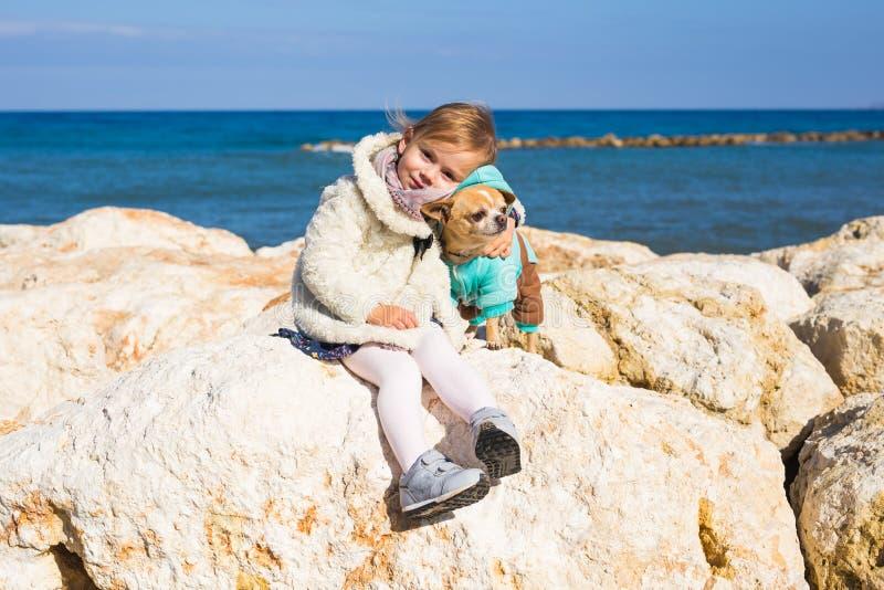 Concept d'enfant, d'animal familier, d'été et de vacances - petite fille avec le chien de chiwawa sur le bord de la mer photos stock