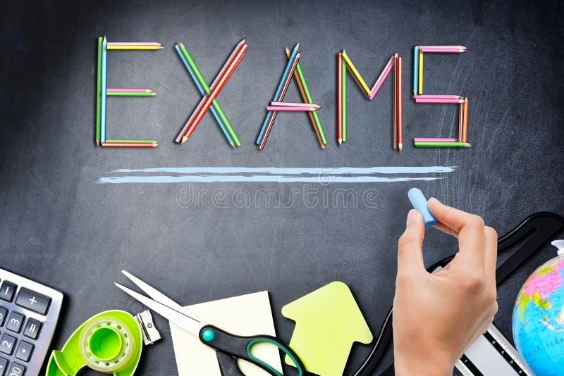 Concept d'examens d'école avec le mot d'examen des crayons colorés sur le fond de tableau noir avec des fournitures scolaires photo libre de droits